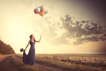 Beautiful girl in blue dress with bouquet and balloons at countryside Stock Photo