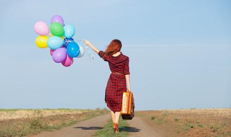 mujer con maleta: Hermosa chica en el vestido a cuadros con globos multicolores y bolso en el campo Foto de archivo
