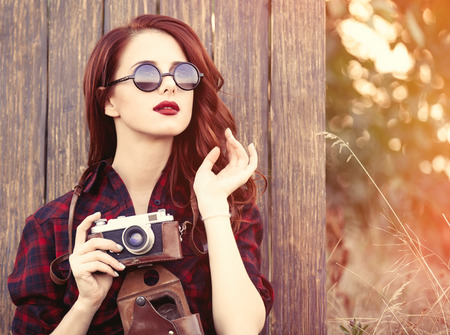 Hermosa chica en el vestido a cuadros con la cámara y las gafas de sol en el fondo de madera.