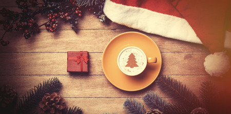 arbol de cafe: Cup of coffee and gift box with pine and hat on wooden table. Foto de archivo