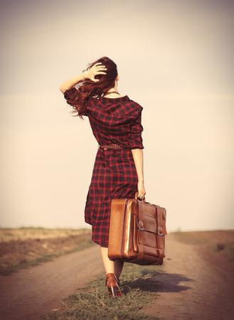 maletas de viaje: Hermosa chica en el vestido a cuadros con el bolso en el campo