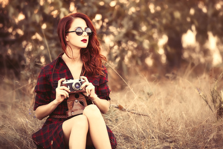 paisaje de campo: Hermosa chica en tela escocesa cámara retro vestido y gafas de sol en el campo