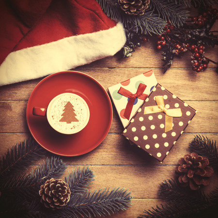 box tree: Cup of coffee and gift box with pine and hat on wooden table. Stock Photo