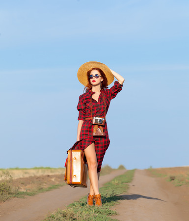 nature photo: Beautiful girl in plaid dress with bag and retro camera on countryside