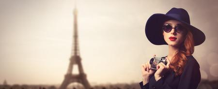 Stil rothaarige Frauen mit Sonnenbrillen und vintage Kamera auf Paris Hintergrund