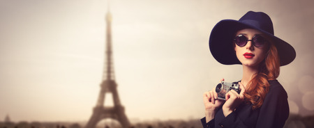 style: Style redhead women with sunglasses and vintage camera on Paris background