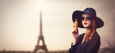 Style redhead girl in a hat holding perfume on Eiffel tower background.