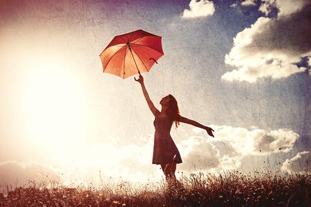 空を背景に傘を持つ若い女性のシルエット 写真素材
