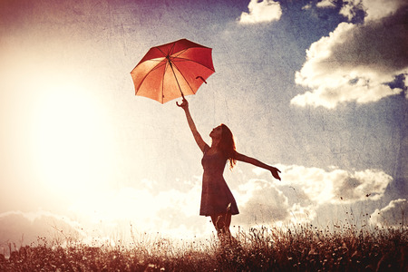 Silhouette of young women with umbrella on sky background