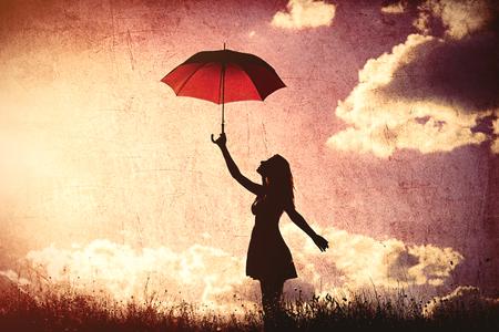 Silueta de la mujer joven con el paraguas en el fondo del cielo Foto de archivo