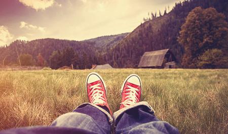 Jonge man in gumshoes en jeans hebben een rust op groen gras in de bergen.