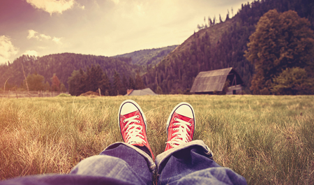 Young man in gumshoes and jeans have a rest on green grass in the mountains.
