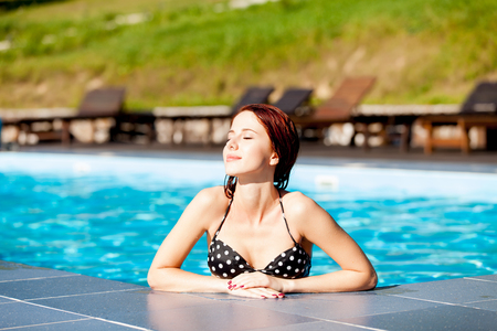 beautiful redhead: Beautiful redhead woman relaxing at swimming pool. Stock Photo