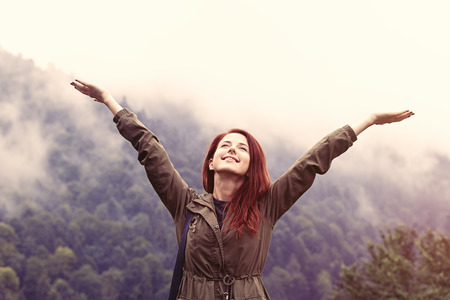 female portrait: Happy redhead girl and mountains on background