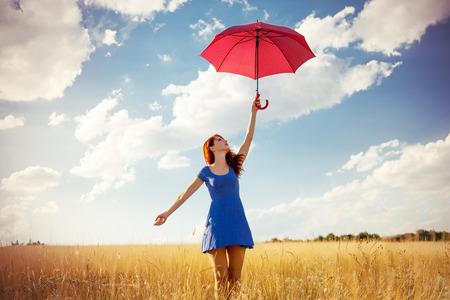 persona feliz: Chica pelirroja hermosa con el paraguas en el campo de otoño
