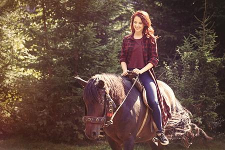 森の中の馬の赤毛の女の子