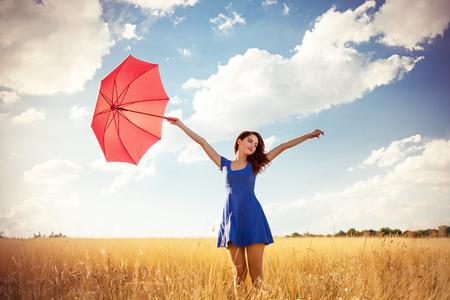 秋の田舎で傘を持つ美しい赤毛の女の子