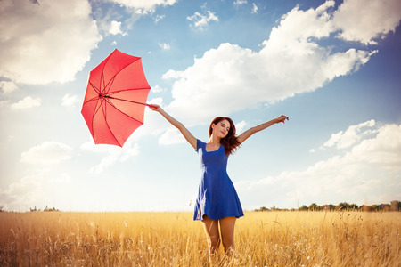 Beautiful redhead girl with umbrella at autumn countryside