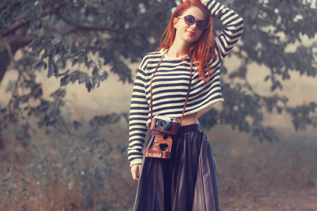 photgraphy: Portrait of a young redhead girl in sunglasses and striped sweater at outdoor in autumn time
