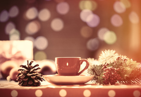 christmas drink: Cup of tea and branch with Christmas lights on background. Stock Photo