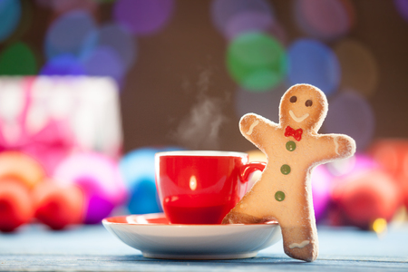 white coffee: Cup of tea and cookie with Christmas lights on background.