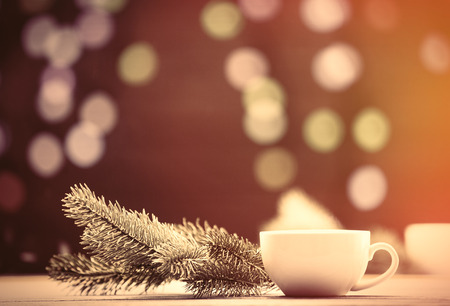 image style: Cup of tea and pine branch with Christmas lights on background.