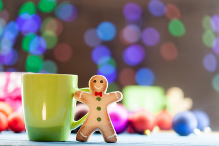 holiday cookies: Cup of tea and cookie with Christmas lights on background.