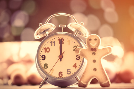 back in time: Vintage clock and cookie with Christmas lights on background Stock Photo