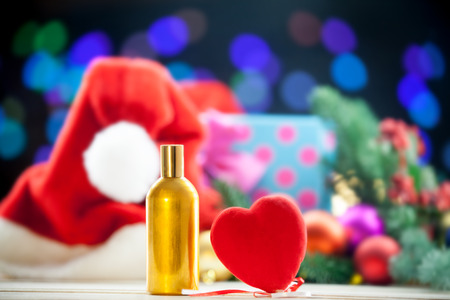 christmas perfume: Heart shape toy and perfume bottle on Christmas lights background.