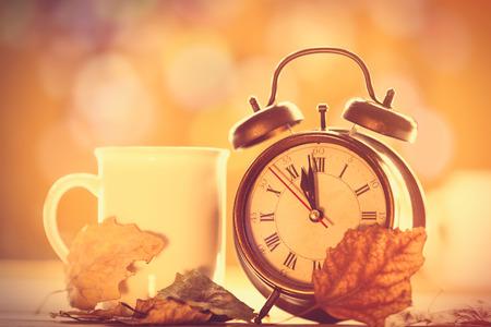 despertador: Reloj alalrm vintage y taza sobre fondo amarillo con el bokeh