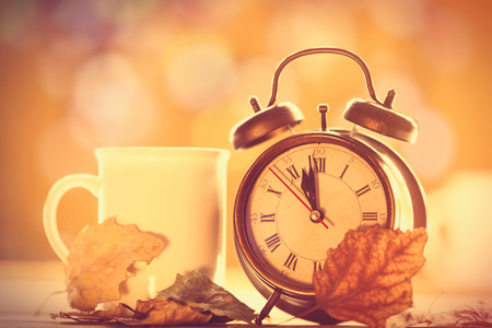 Vintage alalrm clock and cup on yellow background with bokeh Stock Photo