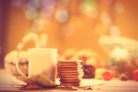 yellow background: Cup of coffee or tea with cookies on autumn background