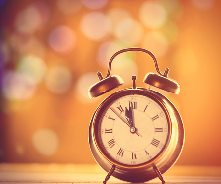 antique background: Vintage alalrm clock on yellow background with bokeh Stock Photo