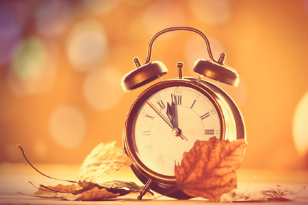 Vintage alalrm clock on yellow background with bokeh Archivio Fotografico
