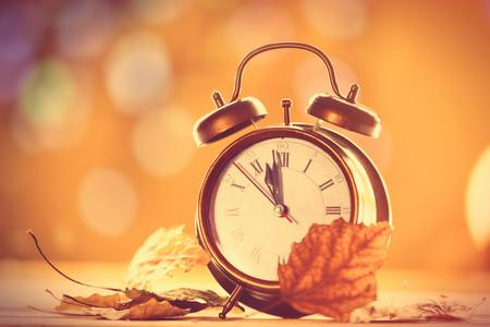hojas antiguas: Reloj alalrm vendimia en fondo amarillo con el bokeh Foto de archivo