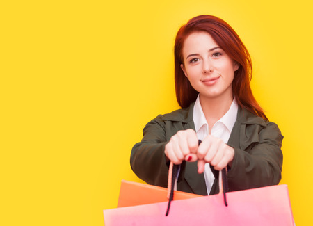woman white shirt: Portrait of a redhead woman with shopping bags on yellow background