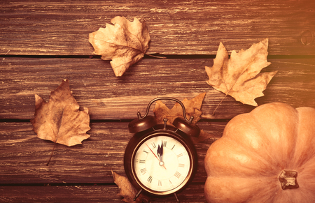 clock: Pumpkin and alarm clock on wooden table