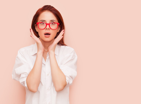 Portrait of surprised redhead woman on pink background
