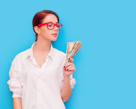 ganancias: Retrato de mujer pelirroja con gafas de color rojo con el dinero en fondo azul Foto de archivo
