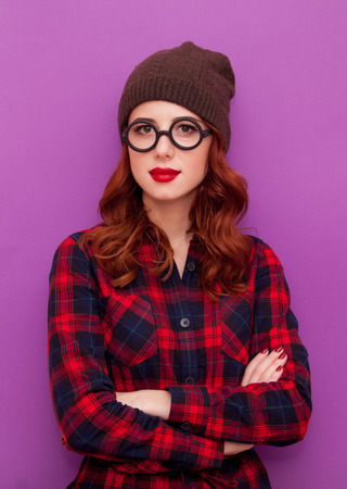girl in red dress: Redhead girl in glasses and hat on purple background Stock Photo