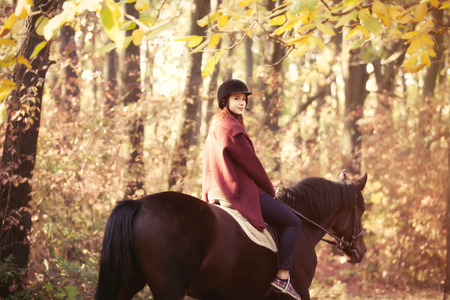 sexual activities: Young girl riding on a black horse in the park