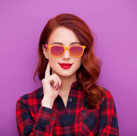 female portrait: Redhead girl in sunglasses on violet background Stock Photo