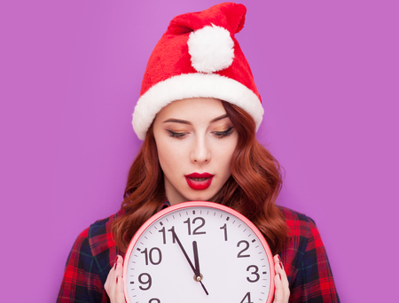 clock: Portrait of a young caucasian girl with Clock on violet background.