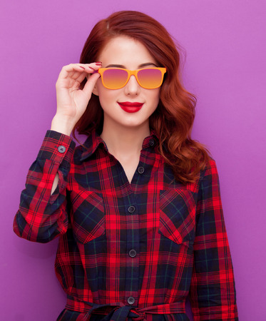 retro lady: Redhead girl in sunglasses on violet background Stock Photo