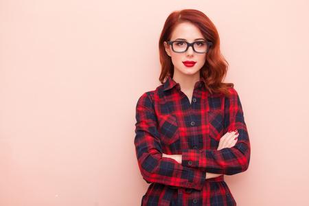 ピンクの背景にメガネの若い白人の女の子の肖像画。