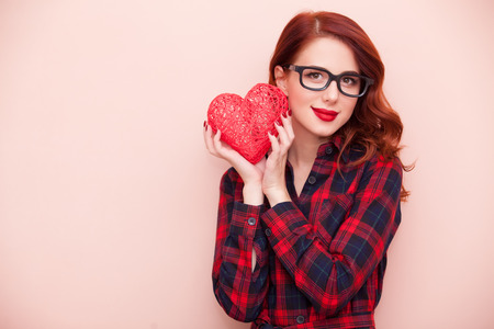 pink hearts: Portrait of a young caucasian girl with gift on pink background. Stock Photo