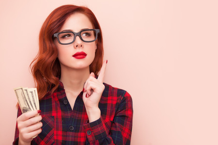 redhead girl in red tartan dress with money on pink background. Standard-Bild