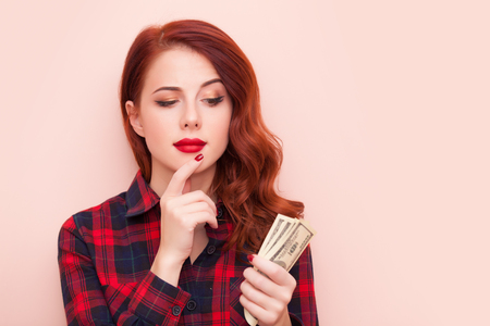 Surprised redhead girl in red tartan dress with money on pink background.