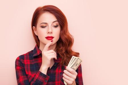 vrouwen: Verrast roodharige meisje in een rode tartan jurk met geld op roze achtergrond. Stockfoto