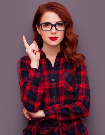 Redhead girl in glasses on grey background